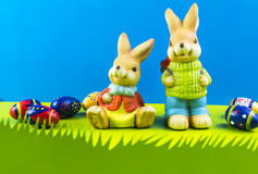 Easter bunnies on blue background. Easter bunnies and colored eggs on blue background Stock Image
