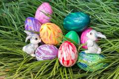 Easter bunnies and colorful eggs. Easter bunnies and eggs on the green grass Stock Images