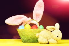 Easter bunnies composition. Hapyy easter holidays eggs and bunny Easter bunnies composition. Toy hare and pink rabbit ears hoop put into a basket full of Easter Stock Photo