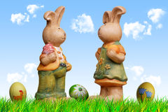 Easter bunnies dolls. Two easter bunny dolls, arranged with grass sky, clouds, eggs and crocuses Stock Photo