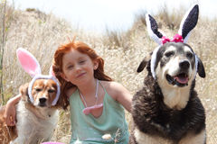 Easter bunnies ears. Young redhead girl with her two pet dogs wearing Easter bunnies ears Royalty Free Stock Photos