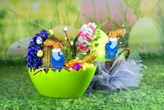 Easter bunnies in egg carts. With green grass , flowers Royalty Free Stock Image