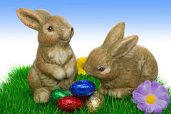 An easter bunnies with eggs. Easter bunnies with eggs on grass with sky blue background Royalty Free Stock Image