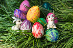 Easter bunnies and eggs close-up. Easter bunnies and eggs hiding in between the green grass Royalty Free Stock Images