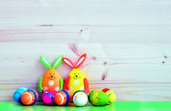 Easter bunnies and eggs. Colored Easter bunnies and eggs on a wodden background Stock Photo
