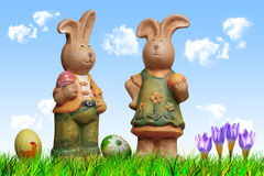 2 Easter Bunnies. With eggs, grass, clouds and spring flowers Royalty Free Stock Photo