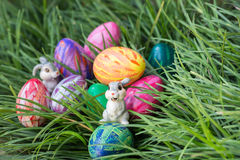 Easter bunnies and eggs on the green grass Stock Images
