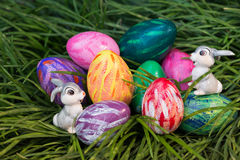 Easter bunnies and eggs on the green grass. Easter bunnies and eggs hiding in between the green grass Royalty Free Stock Image