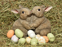 Easter bunnies and eggs. Easter bunnies siiting in hay with colourful eggs around them Stock Image