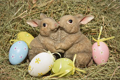 Easter bunnies and eggs. Easter bunnies siiting in hay with colourful eggs around them Royalty Free Stock Image