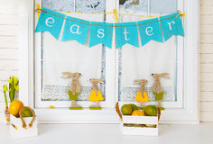 Easter bunnies and eggs. On the window Stock Photography