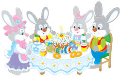 Easter bunnies at a festive table. Family of rabbits celebrating Easter at the holiday table with a fancy holiday cake and colorfully painted eggs Royalty Free Stock Photo