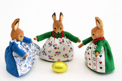 Easter bunnies with golden egg. Three wooden easter bunnies with the golden egg royalty free stock photos
