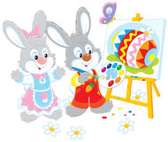 Easter Bunnies painters. Little rabbits drawing a colorful Easter egg on a canvas Royalty Free Stock Images