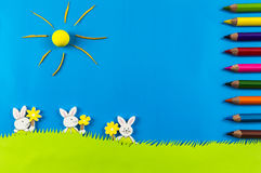 Easter bunnies on blue background. Easter bunnies playing on grass on blue background Royalty Free Stock Photos