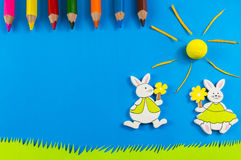 Easter bunnies on blue background. Easter bunnies playing on grass on blue background Stock Photos