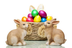 Easter bunnies sitting in front of easter eggs. Two Easter bunnies sitting in front of basket full of colourful Easter  eggs. Isolated on white background Royalty Free Stock Photos