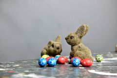 Easter bunnies surrounded by small Easter eggs. Two light brown Easter bunnies on a stained table together with small Easter eggs made of chocolate. The Easter royalty free stock photo