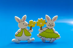 Easter bunnies on blue background. Easter bunnies with yellow flowers on blue background Royalty Free Stock Image