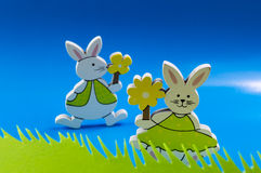 Easter bunnies on blue background. Easter bunnies with yellow flowers on blue background Stock Image