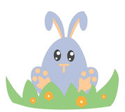 Easter bunny. Cute little egg-headed Easter bunny seated beside an in bloom bush Stock Photo