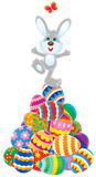 Easter Bunny. Dancing on the top of a hillock of colorful painted eggs Royalty Free Stock Photos