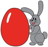 Easter Bunny. Little bunny holding a big red egg Stock Photos