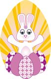 Easter Bunny. Cute white easter bunny with decorated easter eggs and bright sunrise background Royalty Free Stock Photo