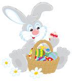Easter Bunny. Funny rabbit with a basket of colorful painted Easter eggs Stock Image