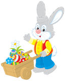 Easter Bunny. Rabbit walking with a hand cart filled with colorfully painted Easter eggs Royalty Free Stock Photo