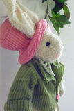 Easter bunny. White female Easter bunny in a pink hat and green jacket, profile; suitable for Easter cards and baby girl birth announcements Royalty Free Stock Photography