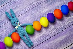 Easter bunny. Amigurumi toy easter bunny with diagonal row of colorful eggs on a wooden table - easter background with copy space Royalty Free Stock Photo