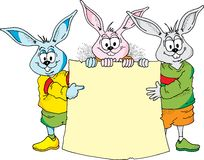 Easter Bunny Announcement. Image of three Easter Bunnies holding a blank sign Stock Photography