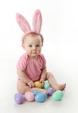 Easter bunny baby. Portrait of a cute baby dressed in Easter bunny ears with a basket full of eggs Stock Images