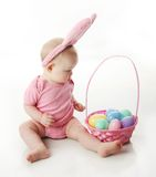 Easter bunny baby. Portrait of a cute baby dressed in Easter bunny ears with a basket full of eggs Stock Photos