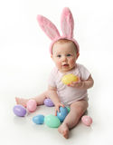 Easter bunny baby. Portrait of a cute baby dressed in Easter bunny ears with pastel eggs Royalty Free Stock Photo