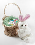 Easter Bunny and Basket 1. A little stuffed Easter Bunny sitting up against an Easter basket filled with fake grass and candy eggs Royalty Free Stock Images