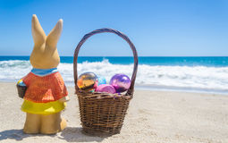 Easter bunny with basket and color eggs on the tropical beach ne Stock Photos