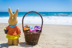 Easter bunny with basket and color eggs on the tropical beach ne Royalty Free Stock Photography