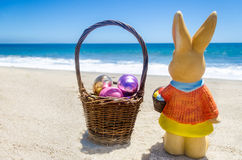 Easter bunny with basket and color eggs on the tropical beach ne Royalty Free Stock Photo