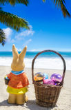 Easter bunny with basket and color eggs on the tropical beach ne Stock Images