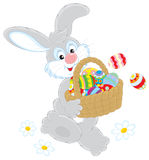 Easter Bunny with a basket of eggs. Grey rabbit friendly smiling and carrying a basket with colorfully painted Easter eggs Stock Photography