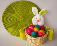 Easter bunny with a basket with painted colorful eggs Royalty Free Stock Photos