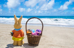 Easter bunny with basketand color eggs on the beach near ocean Stock Images