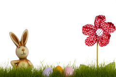 Easter bunny behind grass with drapery flower and Royalty Free Stock Image