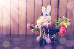 Easter bunny on a bicycle with flowers. Stock Photo