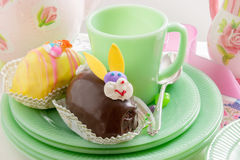 Easter bunny cake with coffee cup and plates. Easter cakes, jelly beans and silver spoon. Holiday themed table setting stock photos