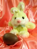 Easter bunny with chocolate egg. A toy bunny with a chocolate egg on pink satin. A cute and sweet Easter image stock photos