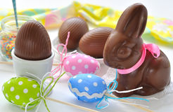 Easter Bunny and chocolate eggs. On a white table Royalty Free Stock Images