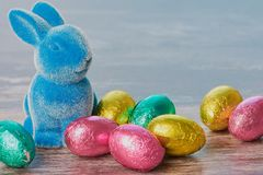 Easter bunny beside chocolate eggs on brown wooden background royalty free stock photography